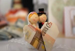 50-Euro-Schein (in Herzform vor einem Brautpaar)