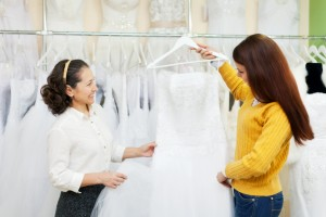 Two women chooses white gown at shop of wedding fashion